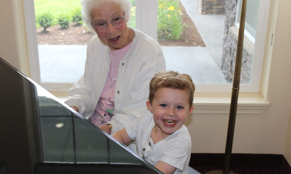 A resident playing piano with a happy child at Paloma Landing Retirement Community in Albuquerque, New Mexico