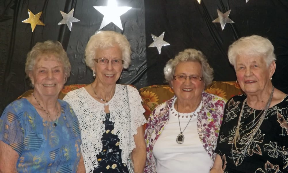 Four residents posing in front of a backdrop at Parker Place in Mentor, Ohio