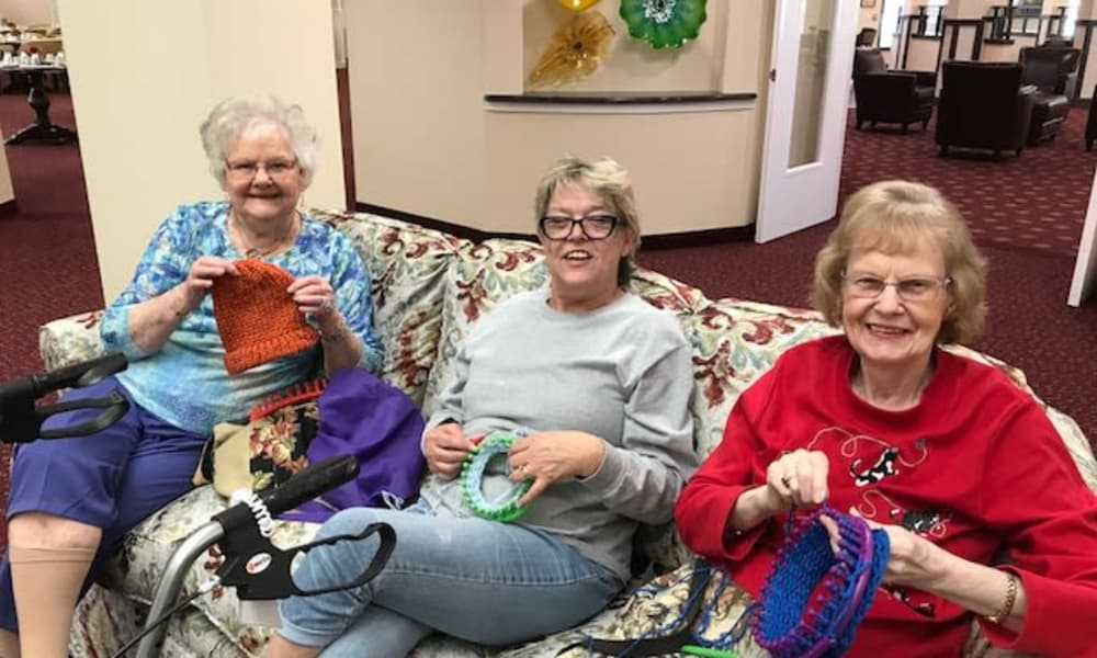 Residents relaxing on the couch making hats together at Rosewood Estates in Cobourg, Ontario