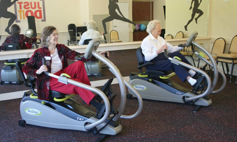 Two residents using the gym equipment at Salishan Gracious Retirement Living in Spring Hill, Florida