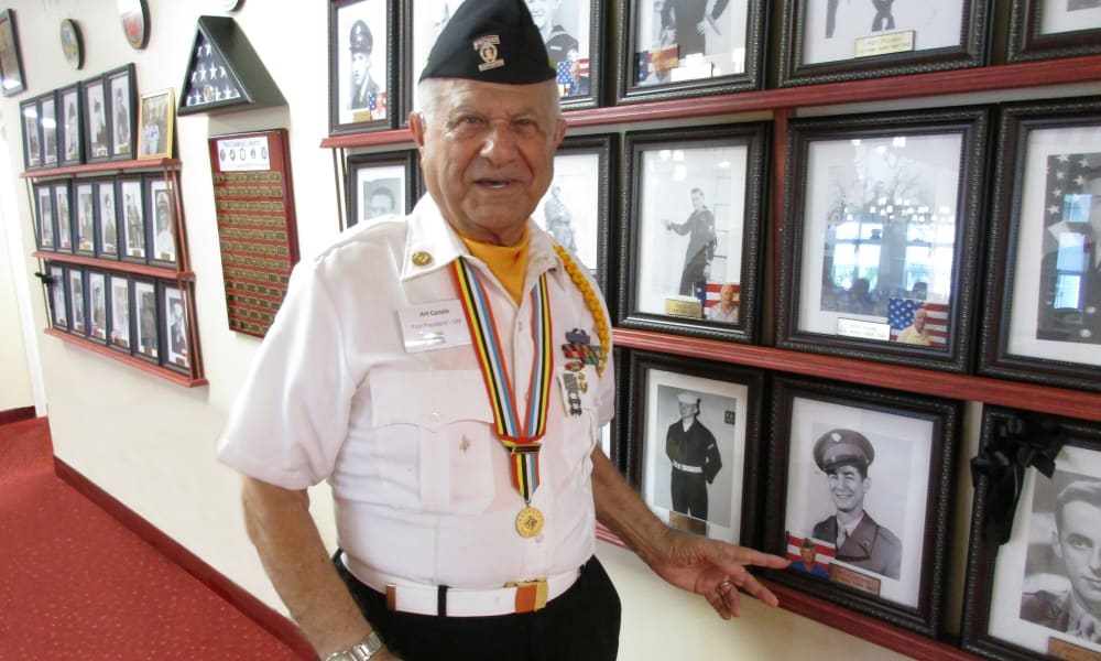 A veteran resident standing next to his photo at Sanford Estates Gracious Retirement Living in Roswell, Georgia