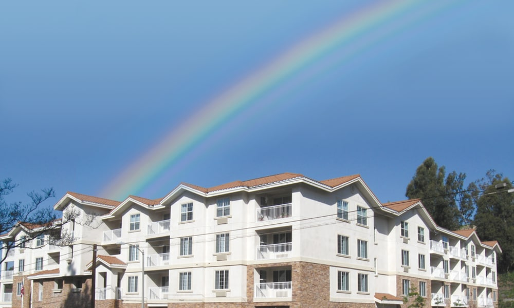 Building exterior with a rainbow in the distance at Scholl Canyon Estates in Glendale, California