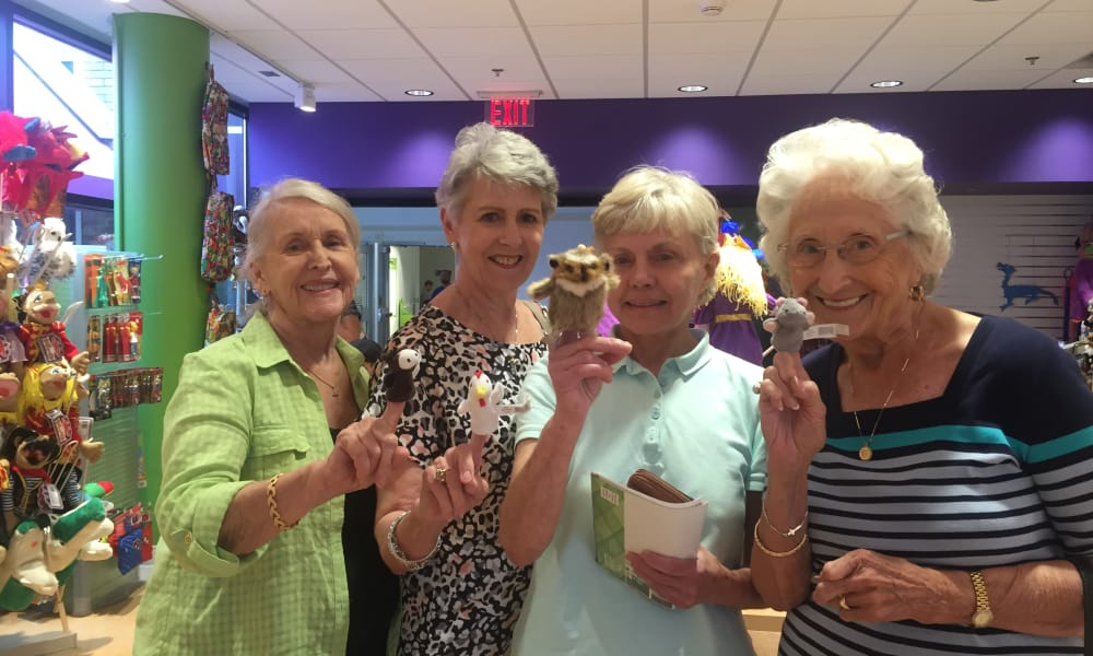 Four residents from Southern Pines Gracious Retirement Living in Southern Pines, North Carolina holding finger puppets in a store