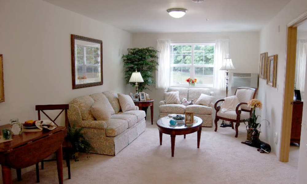 An apartment living room leading to the bedroom at Steeplechase Retirement Residence in Oxford, Florida