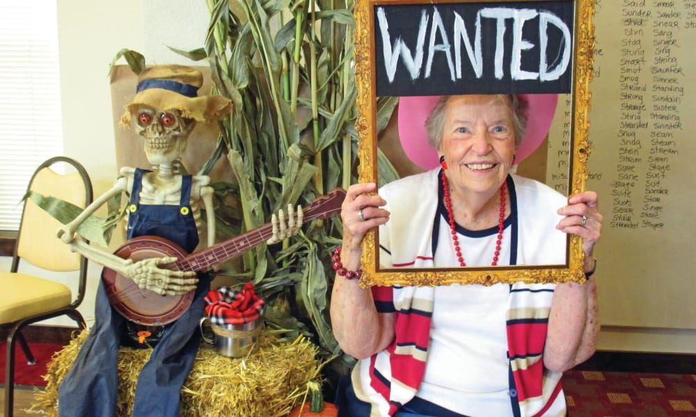 A resident posing with a wanted sign prop at Steeplechase Retirement Residence in Oxford, Florida