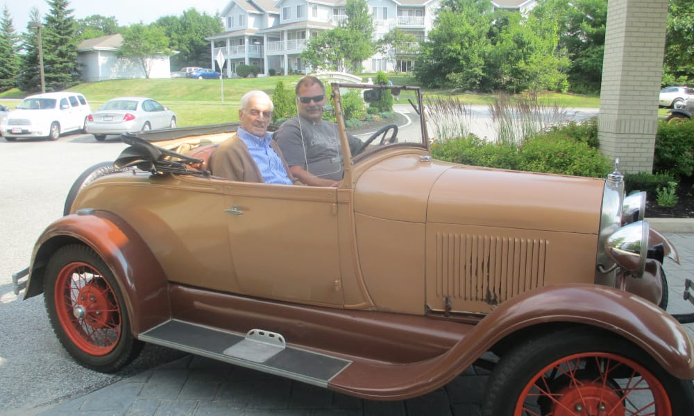 A resident in a classic car in front of Sterling Heights Gracious Retirement Living in Bethlehem, Pennsylvania