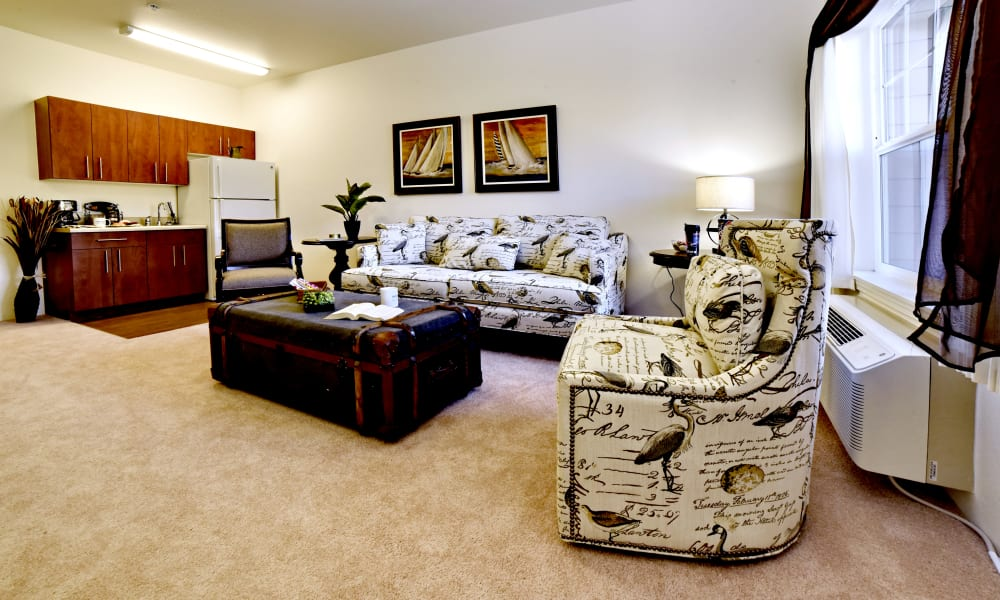 A spacious living room and open kitchen at Sterling Heights Gracious Retirement Living in Bethlehem, Pennsylvania