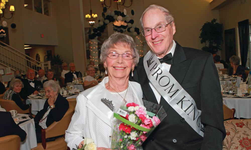 Prom king and queen posing for a photo at Stoneridge Gracious Retirement Living in Cary, North Carolina