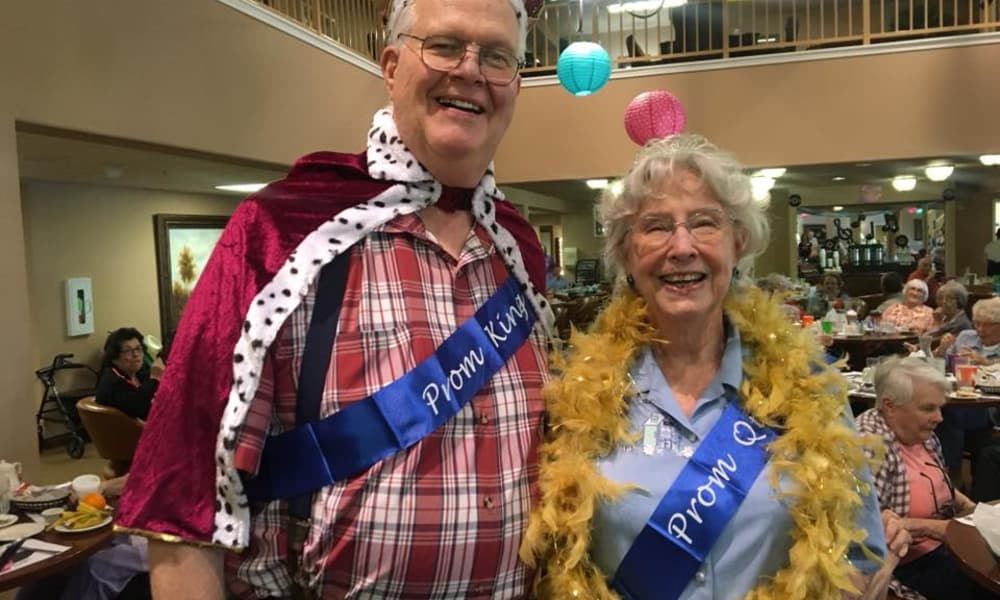 Prom king and queen posing for a photo at Summerville Estates Gracious Retirement Living in Summerville, South Carolina