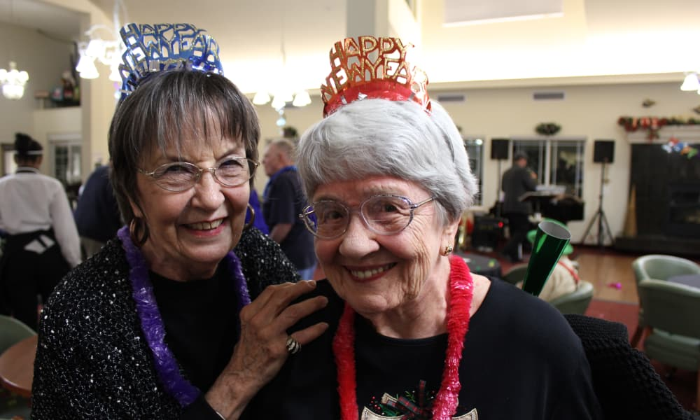 Two residents wearing happy new year hats at Summit Glen in Colorado Springs, Colorado