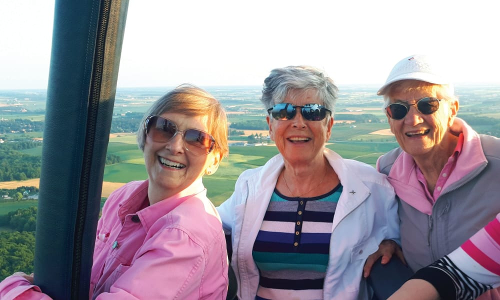 Three residents from The Carriage House Gracious Retirement Living in Oxford, Florida in a hot air balloon with a beautiful view
