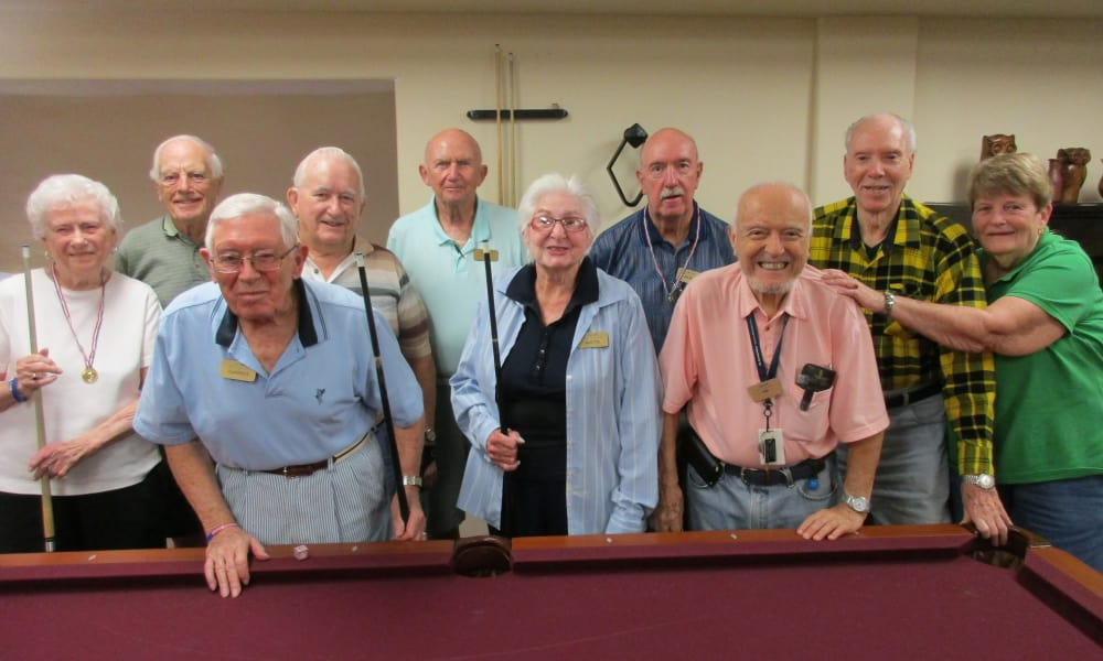 A group of residents in the game room behind the billiards table at The Carriage House Gracious Retirement Living in Oxford, Florida