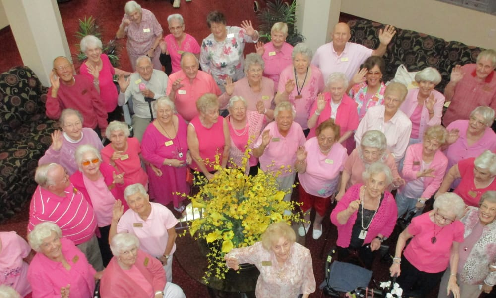 Residents dressed in pink for a group photo at The Carriage House Gracious Retirement Living in Oxford, Florida