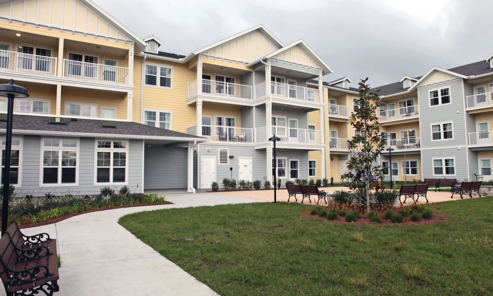 Building exterior with a walkway and outdoor seating at The Carriage House Gracious Retirement Living in Oxford, Florida