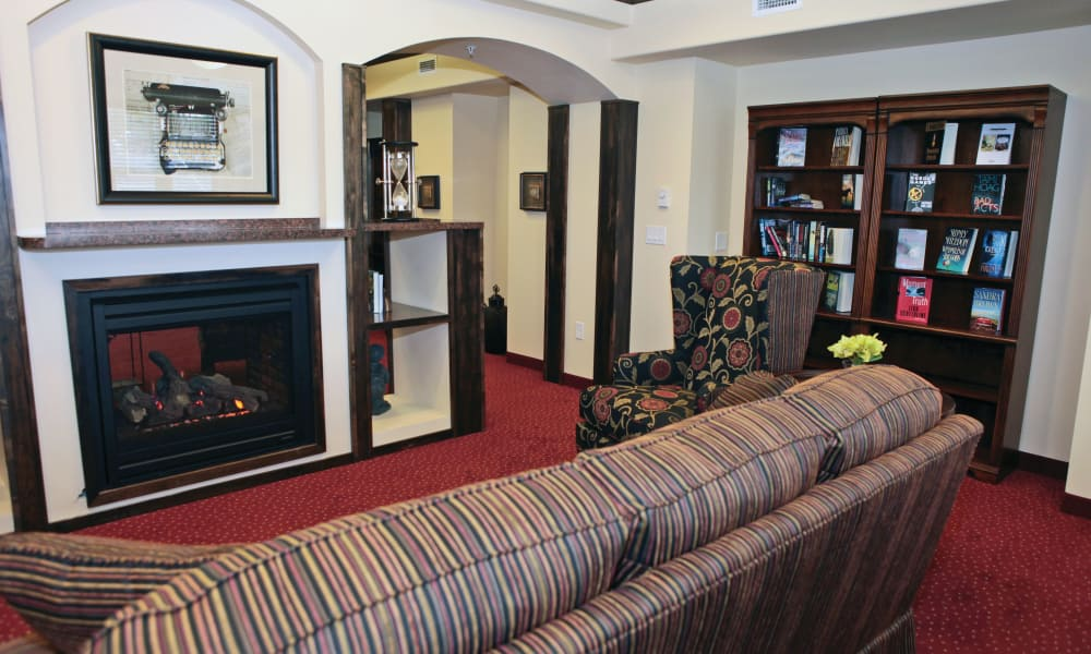 Fireside seating in the reading room at The Carriage House Gracious Retirement Living in Oxford, Florida