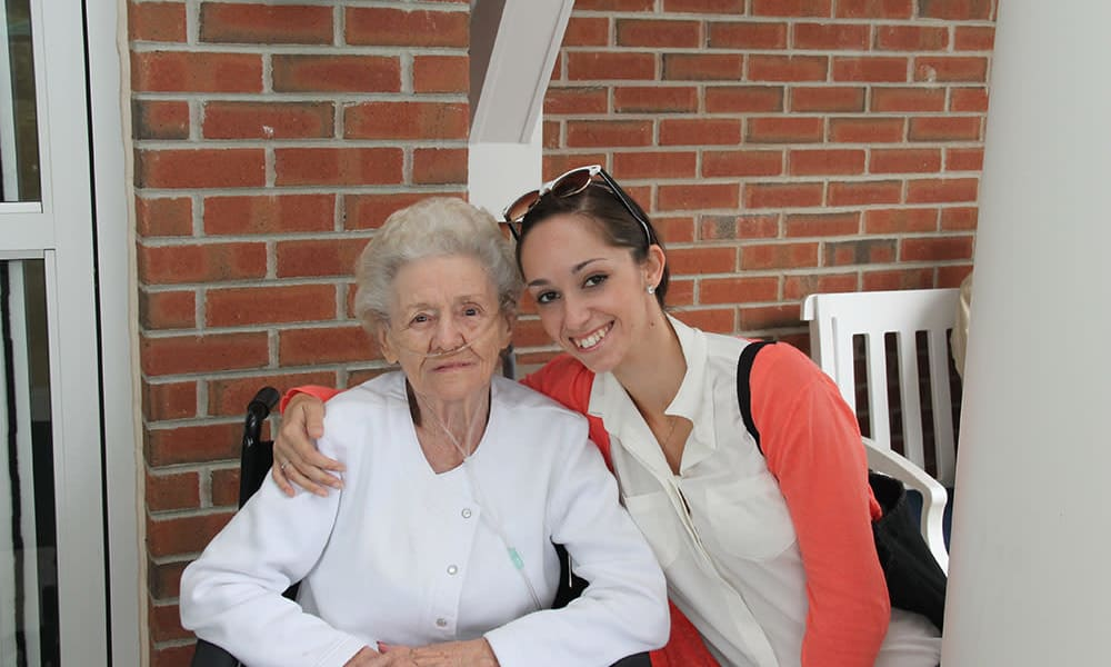 Resident and caretaker sitting on a bench at The Birches at Harleysville in Harleysville, Pennsylvania