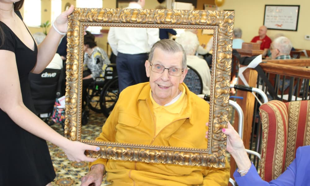 Resident posing in a photo frame at The Birches at Newtown in Newtown, Pennsylvania