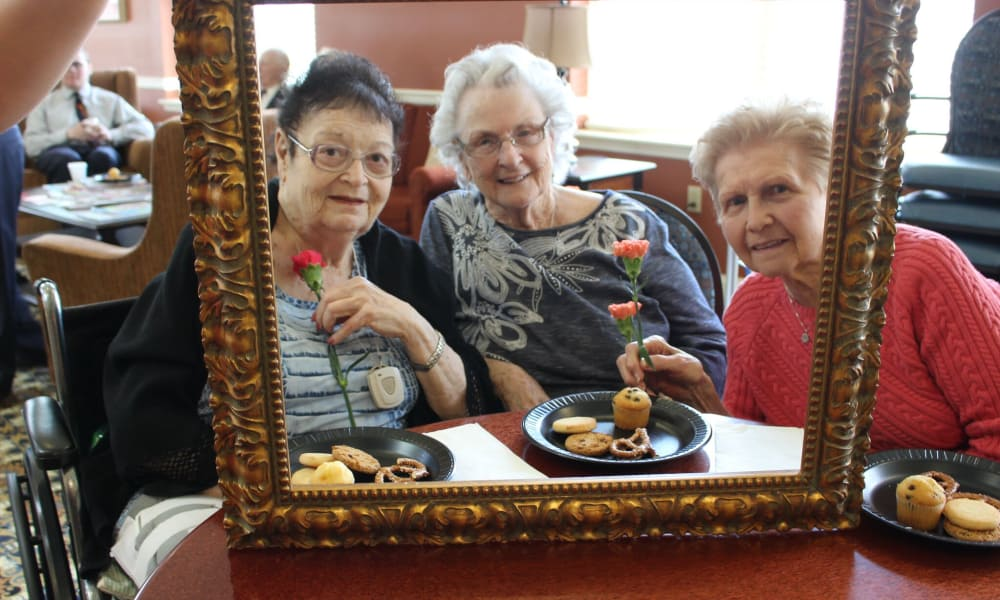 Three residents posing in a photo frame at The Birches at Newtown in Newtown, Pennsylvania