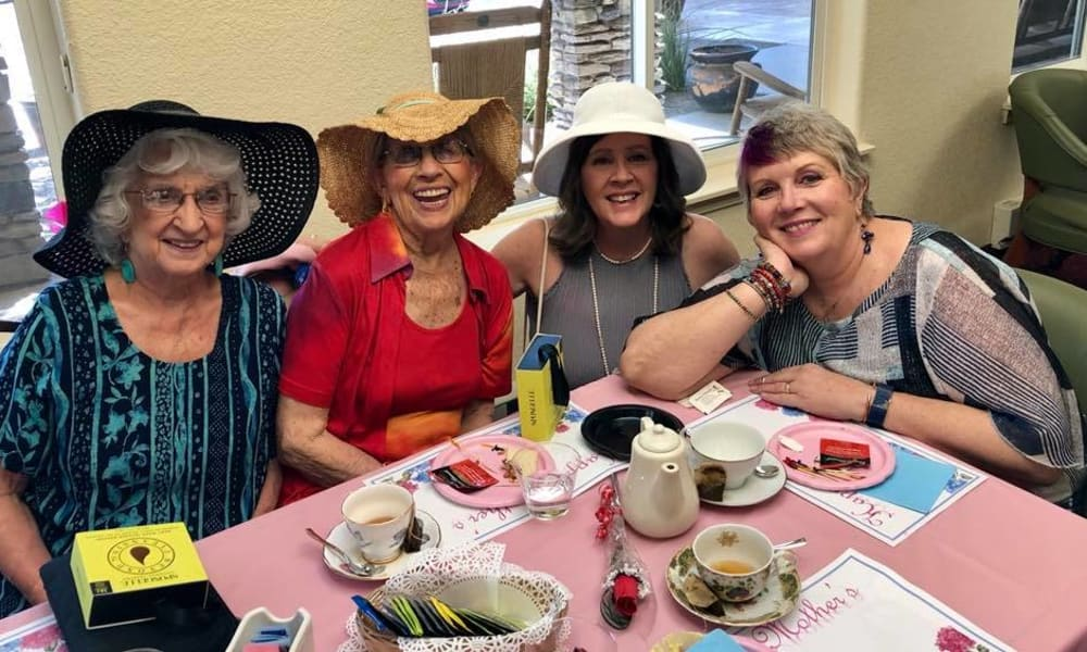 Residents with hats having a tea party at The Oaks Gracious Retirement Living in Georgetown, Texas