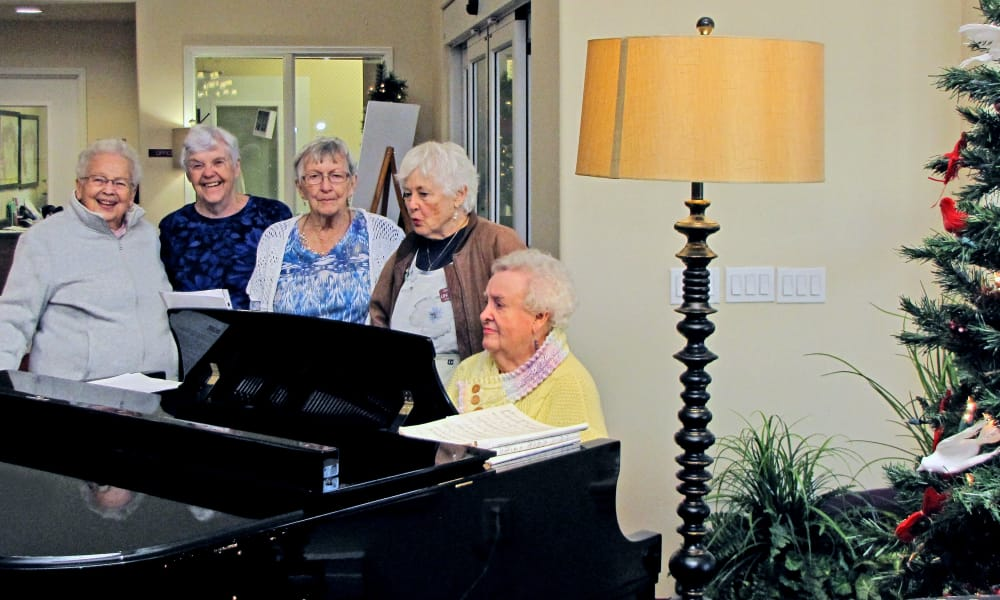 A resident playing piano for other residents at The Rio Grande Gracious Retirement Living in Rio Rancho, New Mexico