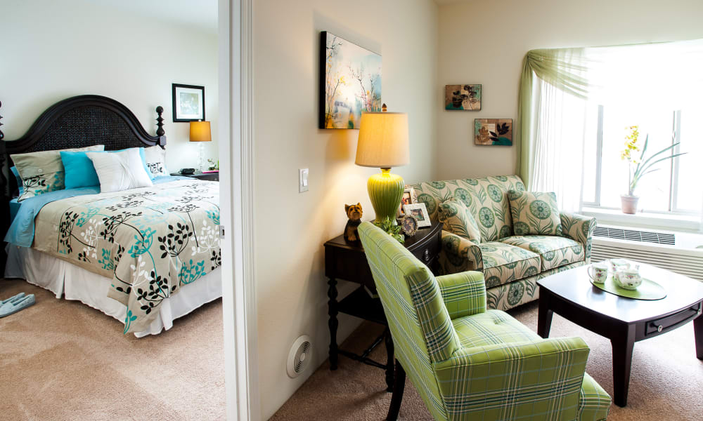 An apartment living room leading to the bedroom at Whispering Pines Gracious Retirement Living in Raleigh, North Carolina