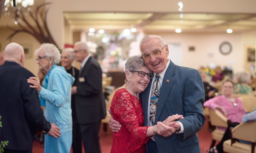 A happy couple slow dancing together at Whispering Pines Gracious Retirement Living in Raleigh, North Carolina