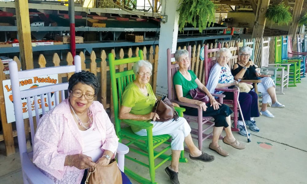 A group of residents from Williams Place Gracious Retirement Living in Davidson, North Carolina sitting in colorful chairs outside of a store