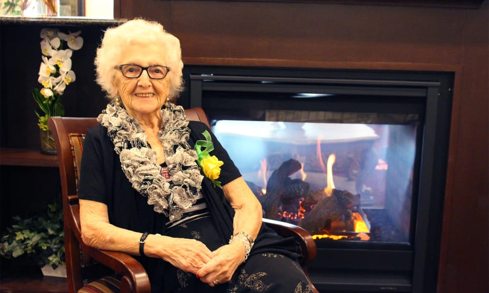 A resident sitting by the fire at Williams Place Gracious Retirement Living in Davidson, North Carolina