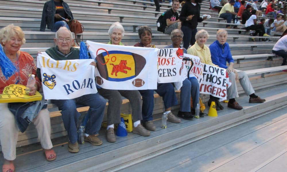 Residents from Willow Creek Gracious Retirement Living in Chesapeake, Virginia holding signs at a football game