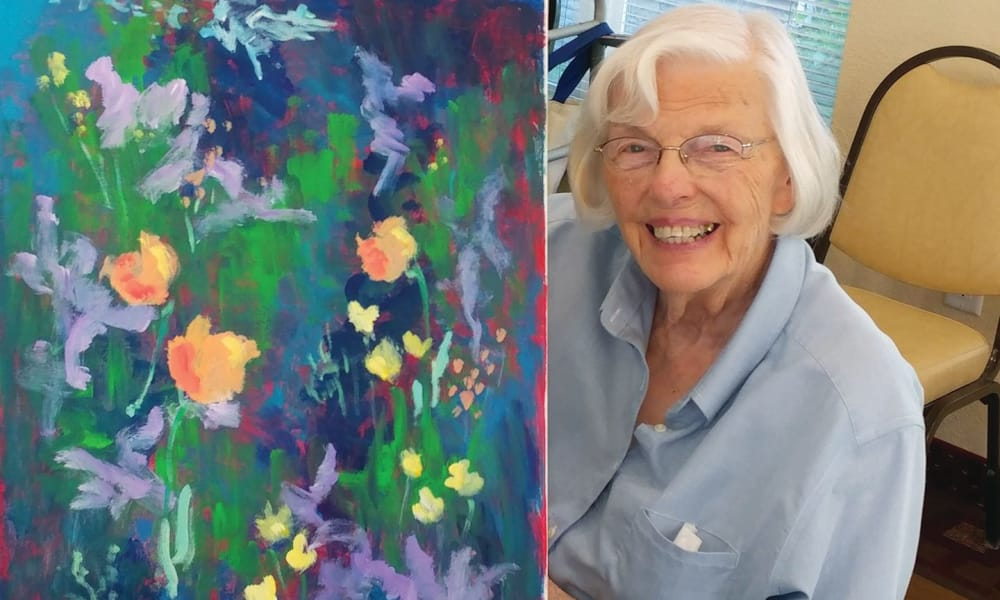 A proud resident holding her floral painting at Mulberry Gardens Assisted Living in Munroe Falls, Ohio