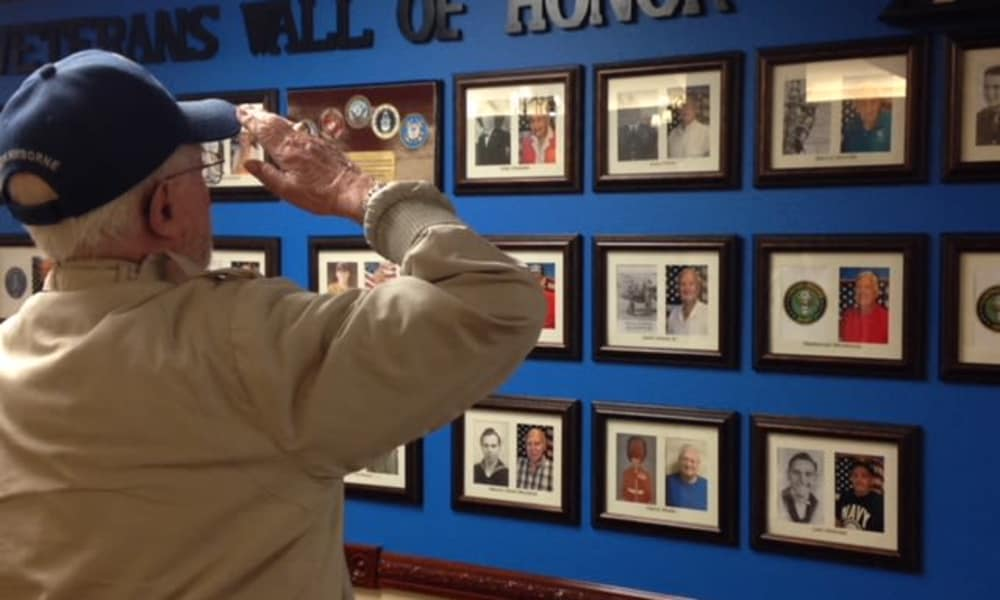 A veteran resident saluting the wall of honor at Mulberry Gardens Assisted Living in Munroe Falls, Ohio