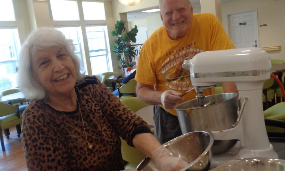 Two happy residents making food together at Mulberry Gardens Memory Care in Munroe Falls, Ohio