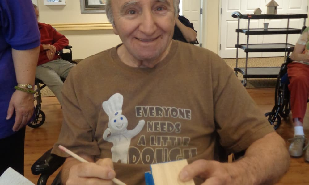 A resident painting a wooden box at Mulberry Gardens Memory Care in Munroe Falls, Ohio