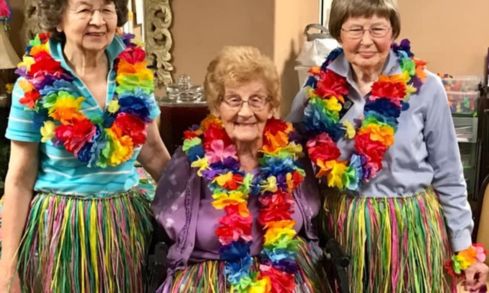 Residents dressed for a tropical party at Mulberry Gardens Memory Care in Munroe Falls, Ohio