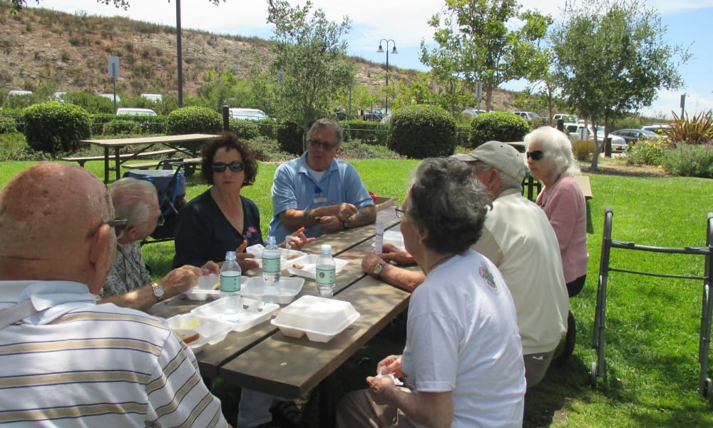 A group of residents eating outside together at Palms at Bonaventure Assisted Living in Ventura, California
