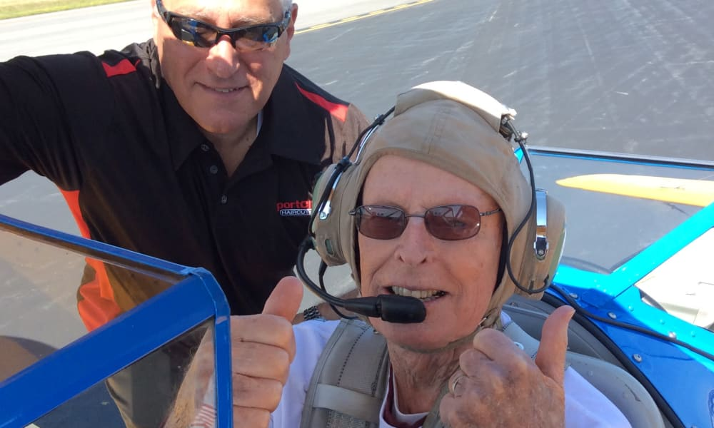 A resident from The Palms at Bonaventure Assisted Living and Memory Care in Ventura, California giving a thumbs up from an airplane