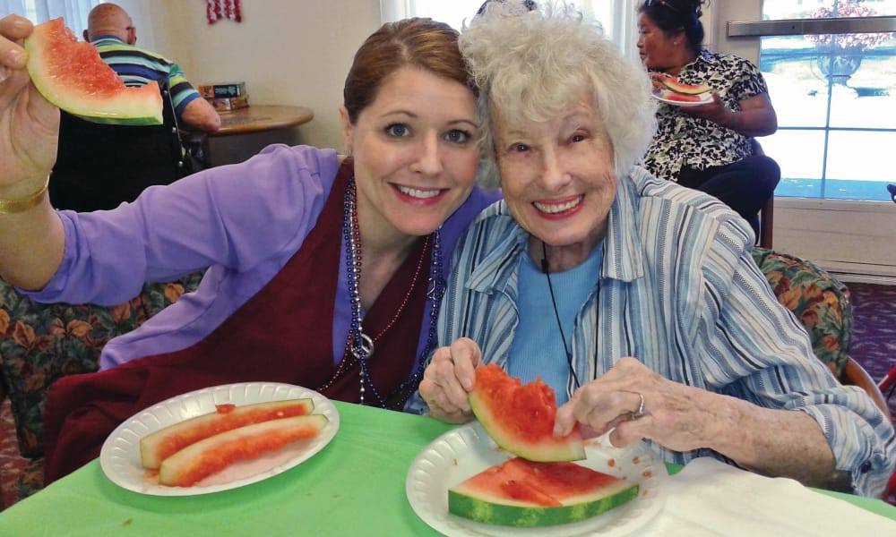 A resident and caretaker eating watermelon at Palms at Bonaventure Assisted Living in Ventura, California