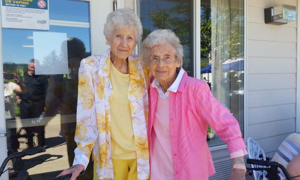 Two residents posing for a photo outside at Somerset Assisted Living in Gladstone, Oregon
