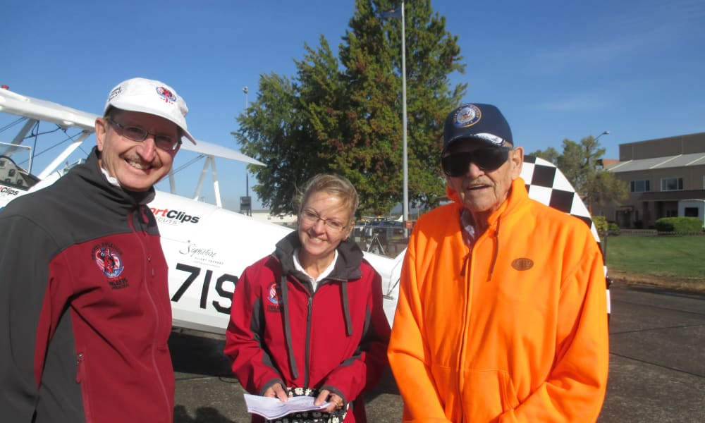 A resident from Stoneybrook Assisted Living in Corvallis, Oregon posing next to a plane