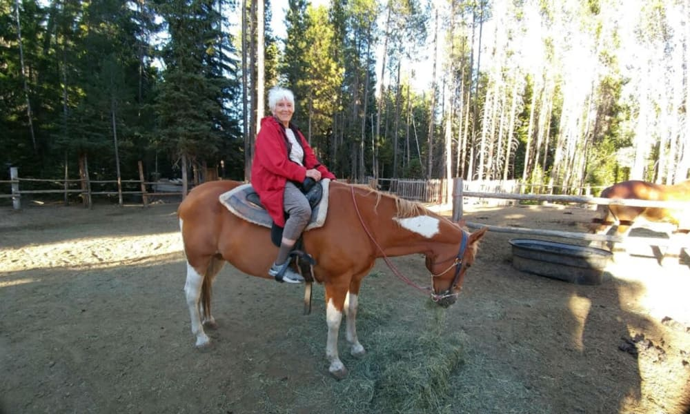 A happy resident from Stoneybrook Assisted Living in Corvallis, Oregon riding a horse