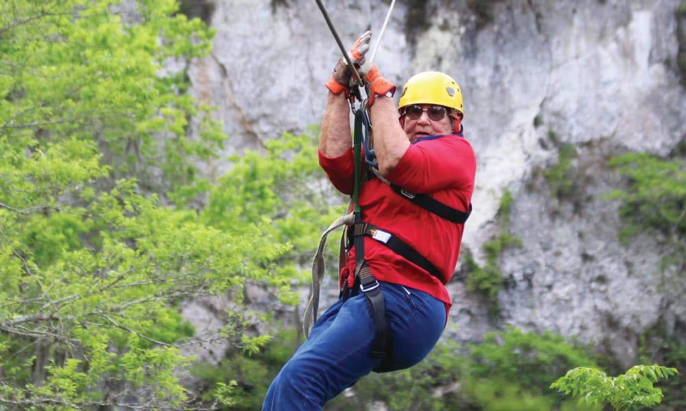 A resident from Stoneybrook Assisted Living in Corvallis, Oregon zip lining from a hillside