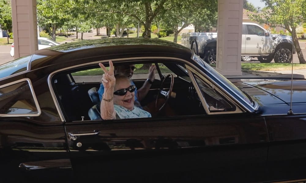 A resident giving a peace sign from inside a classic car at Stoneybrook Assisted Living in Corvallis, Oregon