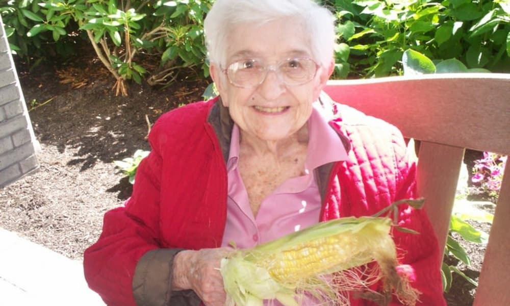 A resident eating corn on the cob on the patio at Winterberry Heights Assisted Living and Memory Care in Bangor, Maine