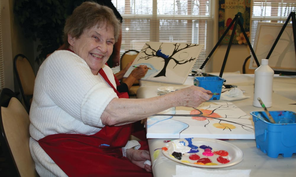 A happy resident painting at Winterberry Heights Assisted Living and Memory Care in Bangor, Maine