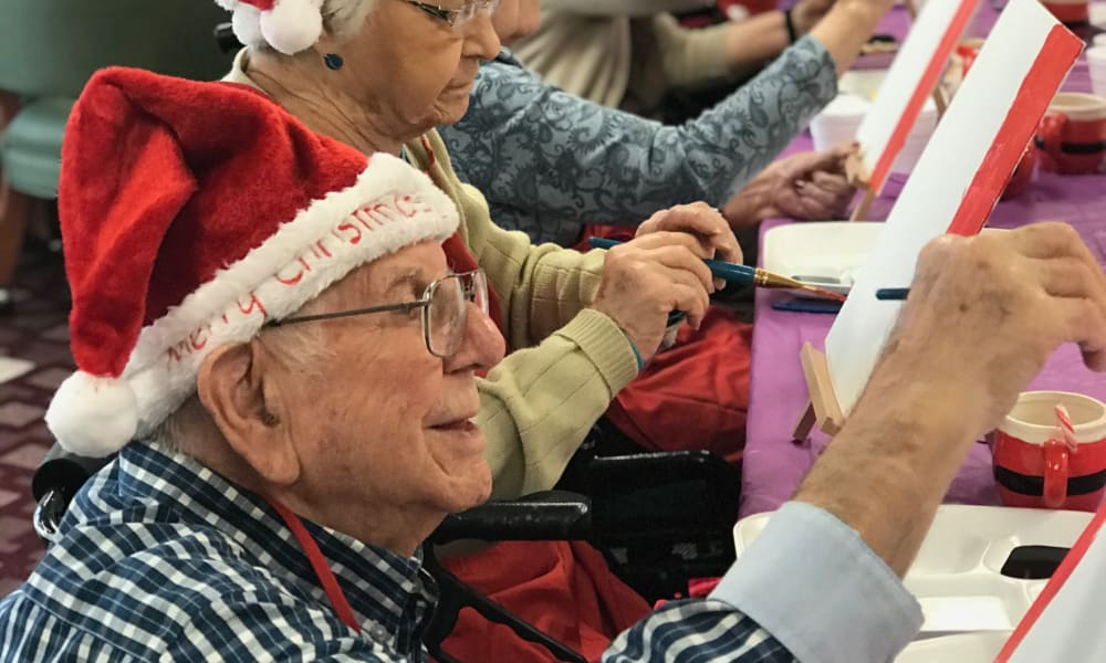 Residents in Santa hats painting together at Amber Park in Pickerington, Ohio