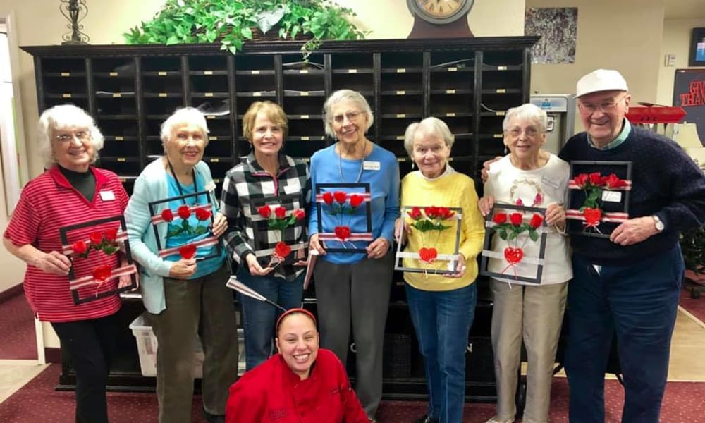 A group of residents holding their floral artwork at Birchwoods at Canco Assisted Living in Portland, Maine