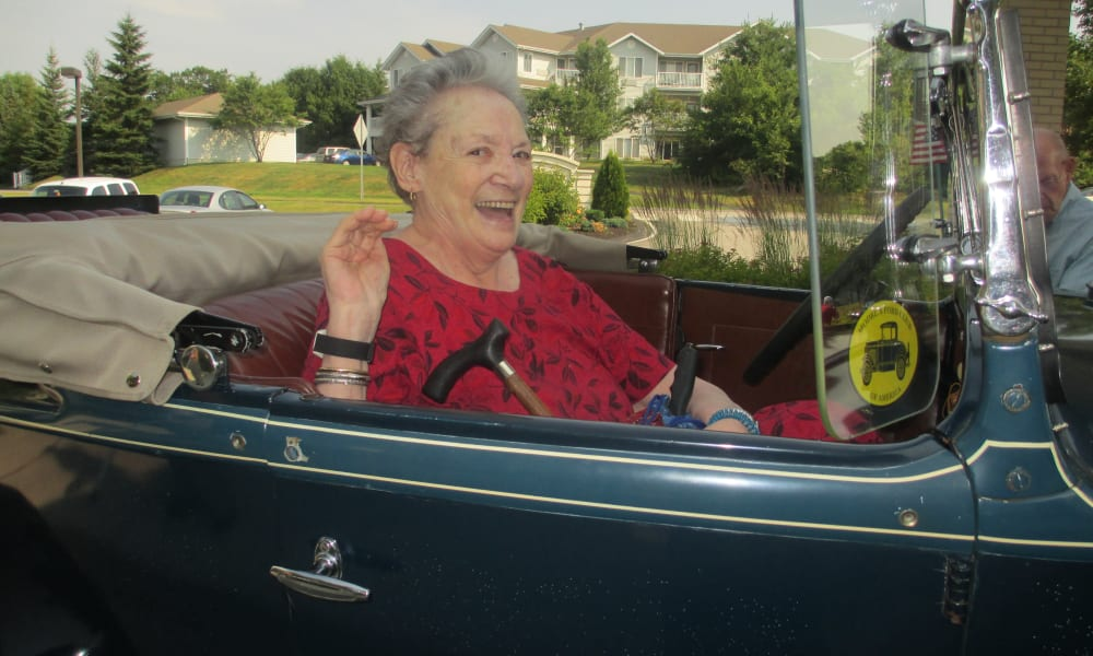 A happy resident in a classic car in front of Birchwoods at Canco Assisted Living in Portland, Maine