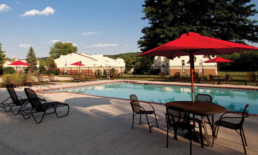 Umbrellas and patio seating next to pool at The Preserve at Milltown in Downingtown, Pennsylvania