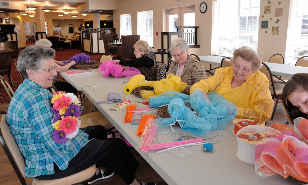 Three residents at Summit Glen in Colorado Springs, Colorado decorating colorful wreaths together