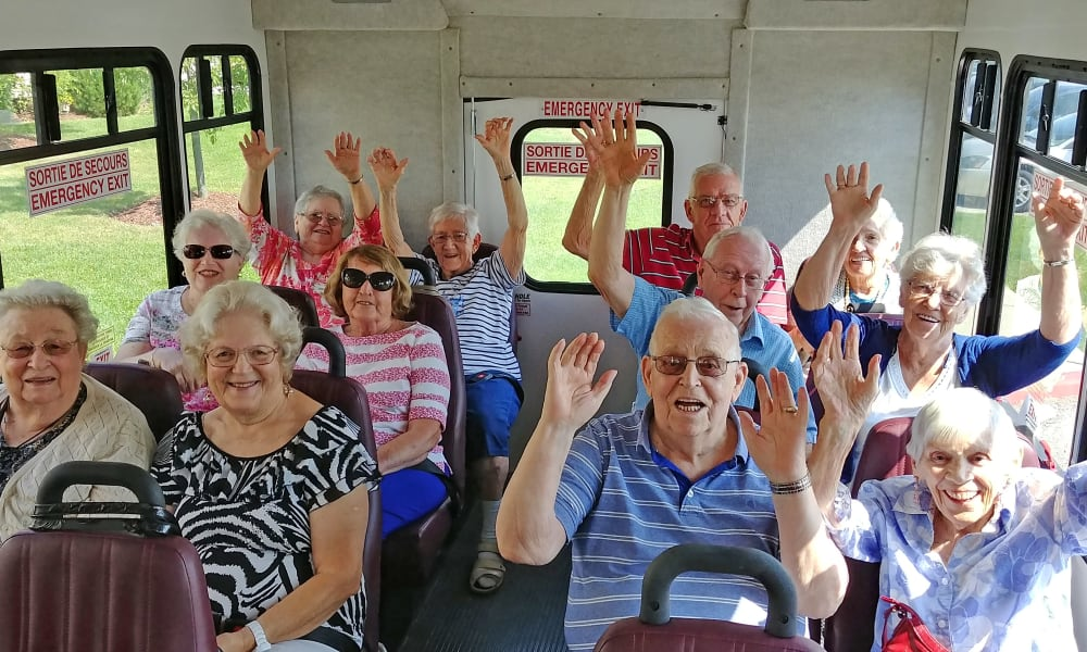 Happy residents with their hands in the air on the community bus at Mulberry Gardens Assisted Living in Munroe Falls, Ohio